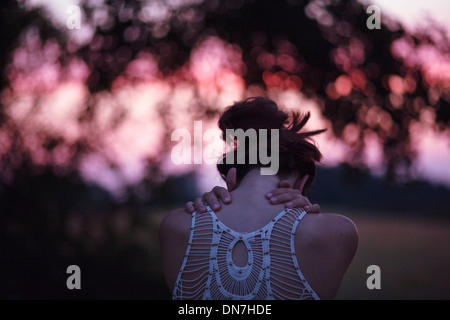 Rear view of a young woman with folded arms - Stock Photo