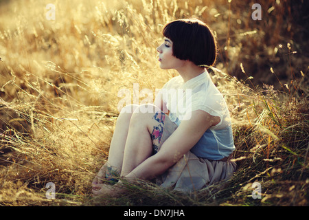 Young woman sitting on a meadow, portrait - Stock Photo