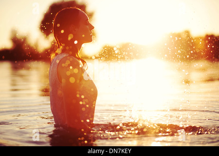 Young woman at sunset in a lake splashing with water - Stock Photo