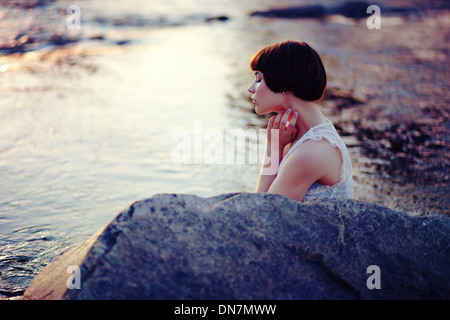 Young woman is sitting on a creek - Stock Photo
