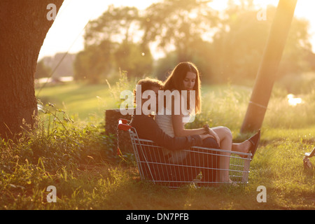 Loving couple sitting in a shopping basket in backlight - Stock Photo