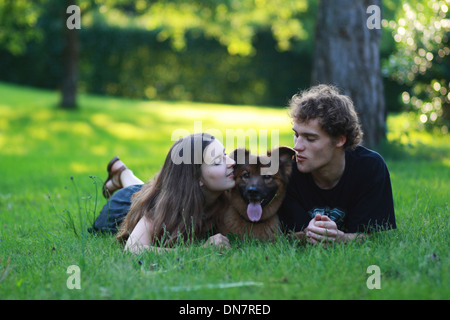 Young couple with a dog lying on a meadow - Stock Photo