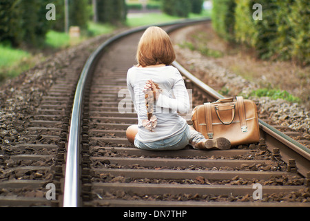 Woman sits on railway track with cut off pigtail in hand - Stock Photo