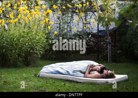 Loving couple lies asleep on a mattress in the garden - Stock Photo