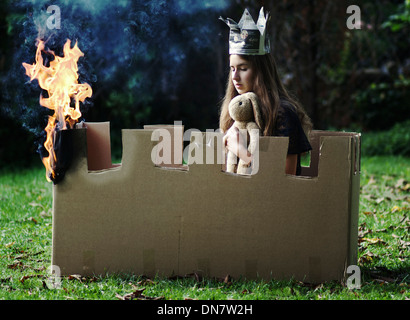 Young girl with plush toy and paper crown sits in a burning castle made ​​of cardboard - Stock Photo