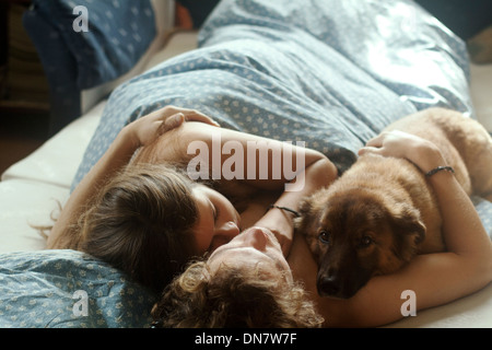 Loving couple lying in bed with dog - Stock Photo