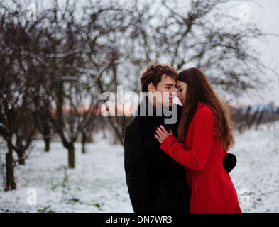 Loving couple arm in arm in snow - Stock Photo