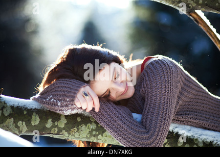 Young woman lying on a tree trunk in snow - Stock Photo