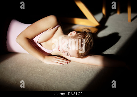 Young woman with closed eyes lying on the floor, portrait - Stock Photo