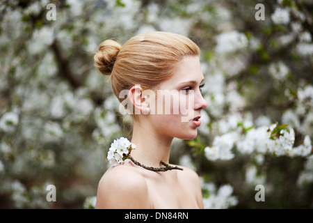 Portrait of a young woman with cherry blossoms - Stock Photo