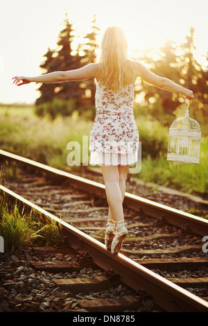 Young woman in dress balancing on a railway track - Stock Photo