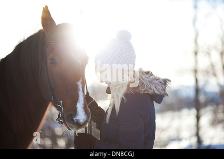 Young woman with horse in winter - Stock Photo