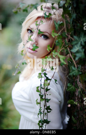 Young woman leaning against a ivy hedge, portrait - Stock Photo