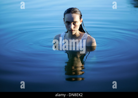 Young woman standing in water, portrait - Stock Photo