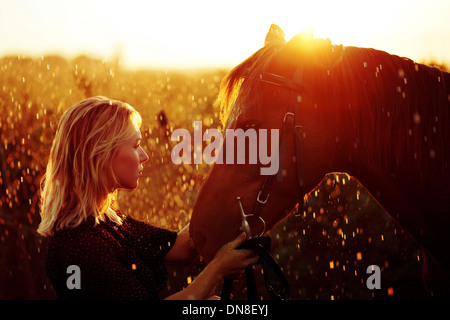 Woman with horse at sunset - Stock Photo