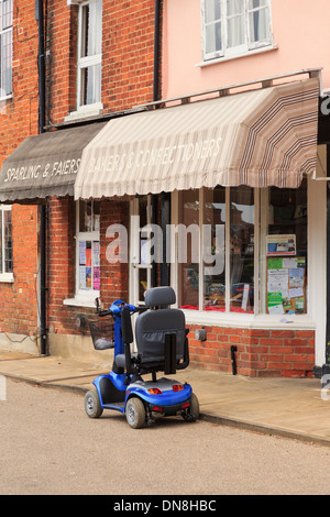 Mobility scooter parked in street outside a village local Baker's shop in Lavenham, Suffolk, East Anglia, England, - Stock Photo