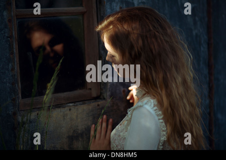 Young woman with reflection in window - Stock Photo