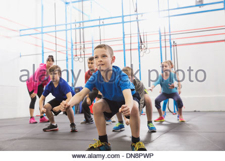 Kids practicing angry gorilla walk in Crossfit class - Stock Photo