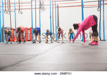 Instructor and children practicing Inchworm - Stock Photo