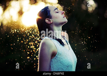 Young woman refreshing herself in the rain - Stock Photo