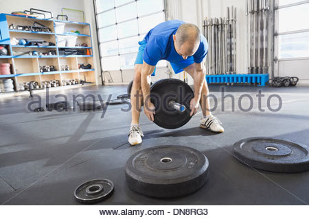 Man adding weight to barbells - Stock Photo