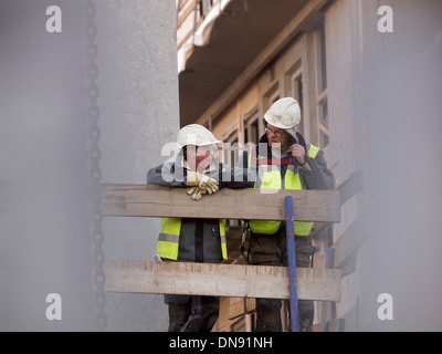 two men chatting on a building construction site in Breda, the Netherlands - Stock Photo