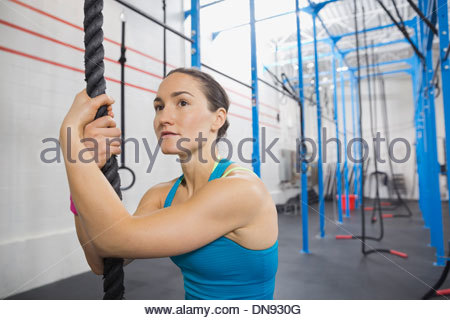 Woman holding rope in Crossfit gym - Stock Photo