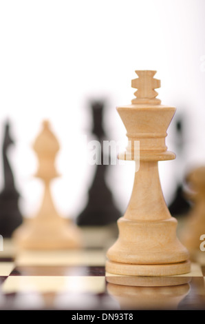 traditional wooden chess pieces on chessboard in different positions - Stock Photo