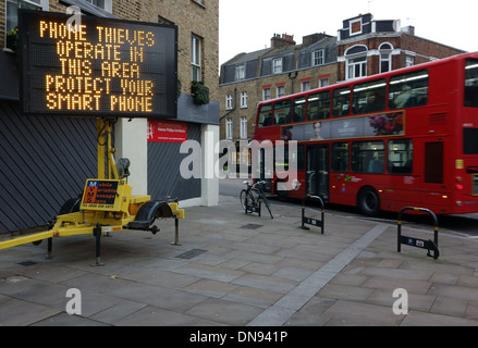 Phone security message on portable sign in London street - Stock Photo
