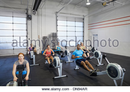 Group using rowing machine in gym - Stock Photo