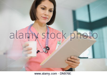 Female nurse reviewing medical records - Stock Photo