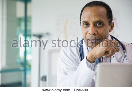 Portrait of confident male doctor in office - Stock Photo