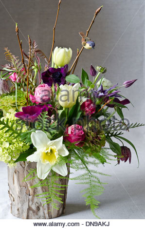 Spring flower arrangement with tulips and daffodils in faux bark vase on light background. - Stock Photo