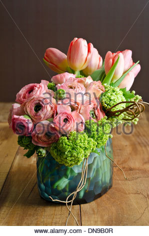 Spring flower arrangement with pink tulips and ranunculus in blue glass vase on wooden table. - Stock Photo