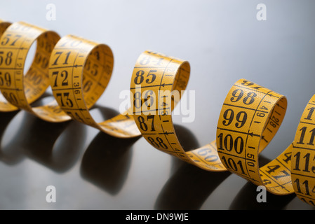 A coiled yellow measuring tape extending out towards the viewer. - Stock Photo