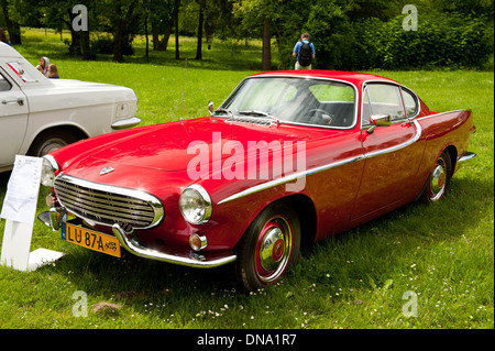 Vintage Red Volvo 1800s car parked on grass - Stock Photo