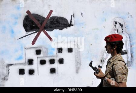 Sanaa, Yemen. 21st Dec 2013. A Yemeni soldier looks at the graffiti of U.S. drone strike painted on a wall as a protest against the drone strikes, in Sanaa, Yemen, on Dec. 21, 2013. The Yemeni parliament on Sunday approved a ban on U.S. drones in the country after dozens of civilians were killed by the unmanned aircraft, the official Saba news agency reported. The decision was made after the U.S. drone mistakenly hit a wedding convey on Thursday in Yemen's southeastern province of al- Bayda, killing up to 17 Yemeni civilians and wounding about 21 others. Credit:  Xinhua/Alamy Live News