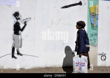 Sanaa, Yemen. 21st Dec 2013. A Yemeni boy looks at the graffiti of U.S. drone strike painted on a wall as a protest against the drone strikes, in Sanaa, Yemen, on Dec. 21, 2013. The Yemeni parliament on Sunday approved a ban on U.S. drones in the country after dozens of civilians were killed by the unmanned aircraft, the official Saba news agency reported. The decision was made after the U.S. drone mistakenly hit a wedding convey on Thursday in Yemen's southeastern province of al- Bayda, killing up to 17 Yemeni civilians and wounding about 21 others. med) Credit:  Xinhua/Alamy Live News