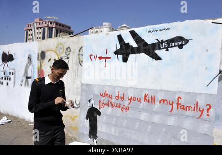 Sanaa, Yemen. 21st Dec 2013. A Yemeni man walks besides the graffiti of U.S. drone strike painted on a wall as a protest against the drone strikes, in Sanaa, Yemen, on Dec. 21, 2013. The Yemeni parliament on Sunday approved a ban on U.S. drones in the country after dozens of civilians were killed by the unmanned aircraft, the official Saba news agency reported. The decision was made after the U.S. drone mistakenly hit a wedding convey on Thursday in Yemen's southeastern province of al- Bayda, killing up to 17 Yemeni civilians and wounding about 21 others. (Xinhua/Mohammed Moha © Xinhua/Alamy L