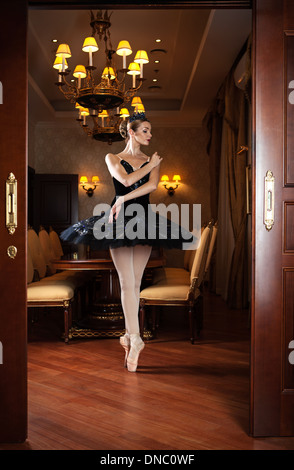 Ballerina in black tutu standing on pointes in doorway in luxury interior - Stock Photo