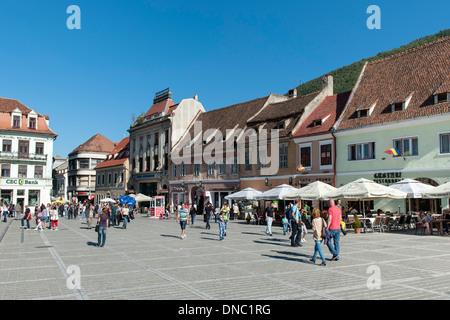 Pedestrians in Brașov Council Square (Piața Sfatului) in the old town in Brasov, a city in the Transylvania region - Stock Photo