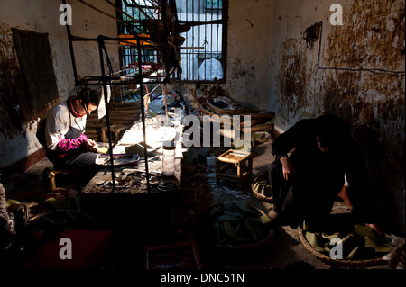 Chongqing, China - 31 December 2010: a run down factory where two workers manufacture shoes. - Stock Photo