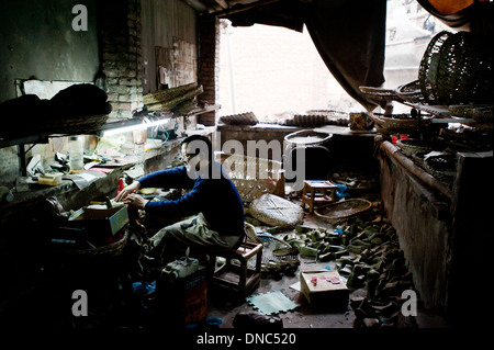 Chongqing, China - 31 December 2010: a man works in a messy shoes factory. - Stock Photo