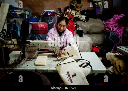 Chongqing, China - 31 December 2010: a chinese woman sews parts of a bag on a sewing machine in a textile factory. - Stock Photo