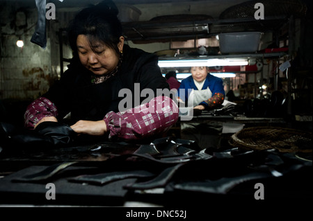Chongqing, China - 31 December 2010: a woman works on boots in a small manufacturing factory producing shoes. - Stock Photo