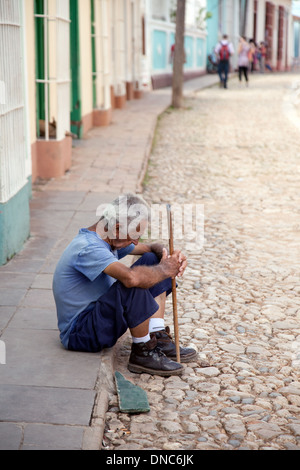 Poor old man sitting in the street, example of poverty in Trinidad, Cuba Caribbean, latin America - Stock Photo