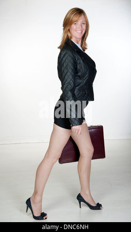 Business woman wearing black carrying a briefcase - Stock Photo
