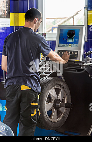 Mechanic in auto centre balancing new tyre on wheel, Slovenia - Stock Photo
