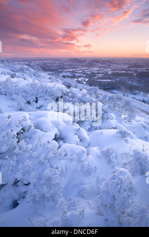 The last rays of sun are lighting up the clouds with a dramatic deep pink. Snow is blown by the wind on the gorse - Stock Photo