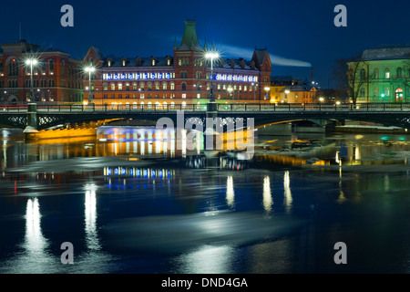 Winter night view of Vasabron and Riddarholmen, seen from Strömgatan, Stockholm.  Melting sheets of ice flow past - Stock Photo